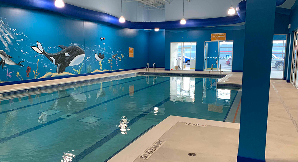 Indoor teaching pool with paintings of whales and fish on the wall at the Goldfish Swim School in Burlington Ontario
